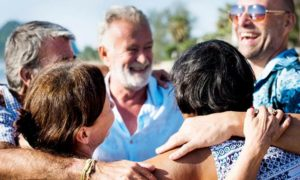 group of senior citizens on a beach happy shoulder to shoulder